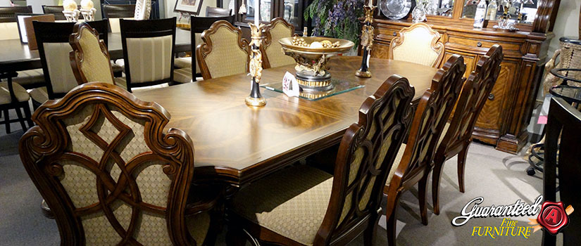 Polished wooden dining table with ornate wooden chairs around it. Furniture is in store showroom.