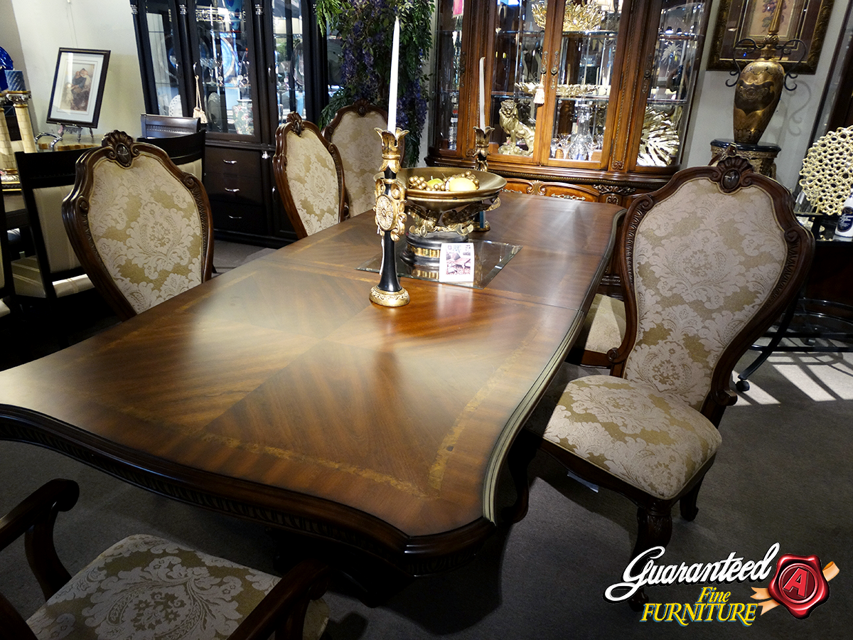 Polished wooden dining table with wooken chairs around it. Furniture in a store showroom.