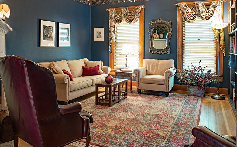A large living room with a long rug, upholstered chairs, a plush sofa, and blue walls.