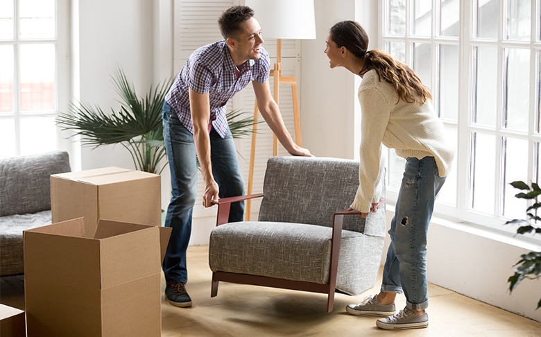 A couple places a modern arm chair near a pair of packing boxes.