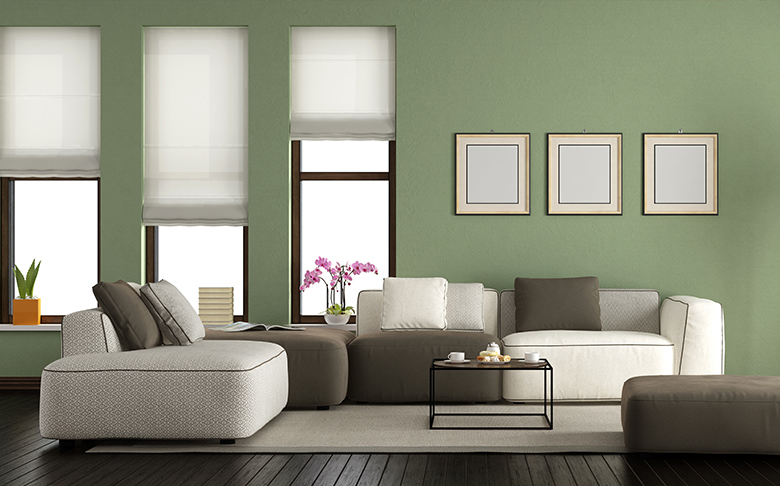 A living room with large modern sofa chairs, tall windows, and mint-green walls.