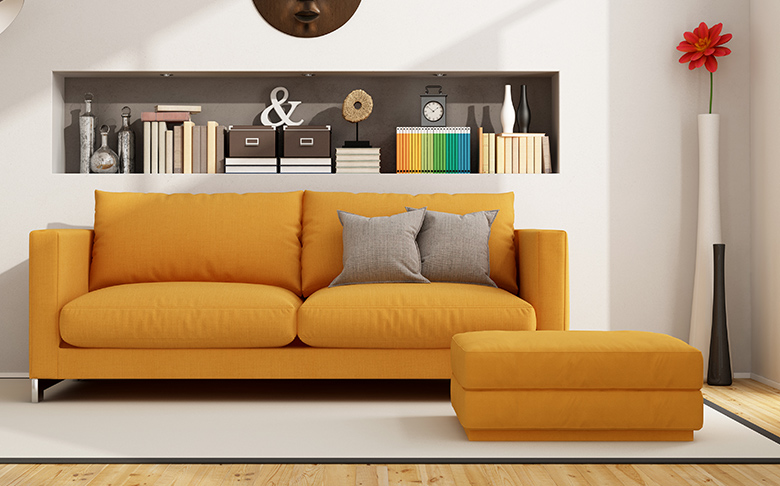 A white living room with a bright orange sofa, ottoman, and lots of decor.