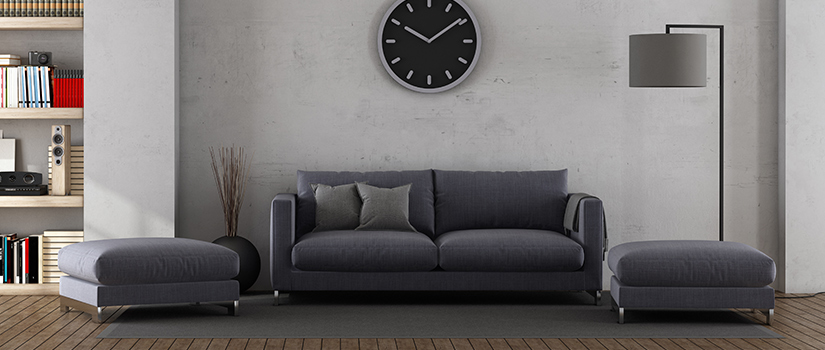 A dark living room with a sofa, two ottomans, a modern lamp, a large clock, and a bookshelf in the distance.