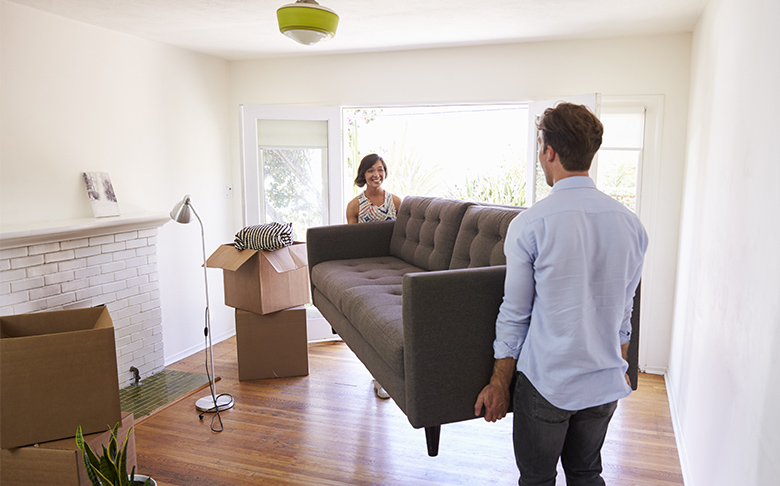 A couple carries a couch closer to a large window as they unpack.