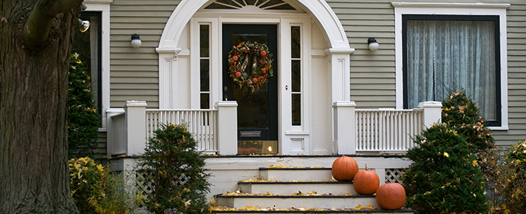 The front door of a white home, adorned with autumn decor.