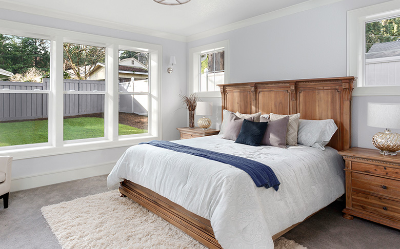 A wide, well-lit bedroom. The bed has a quality wooden headboard.