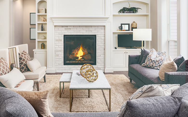 A coffee table in a bright, white room with a fireplace.