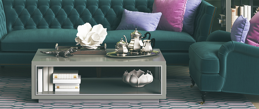 A modern coffee table in front of a dark green couch.
