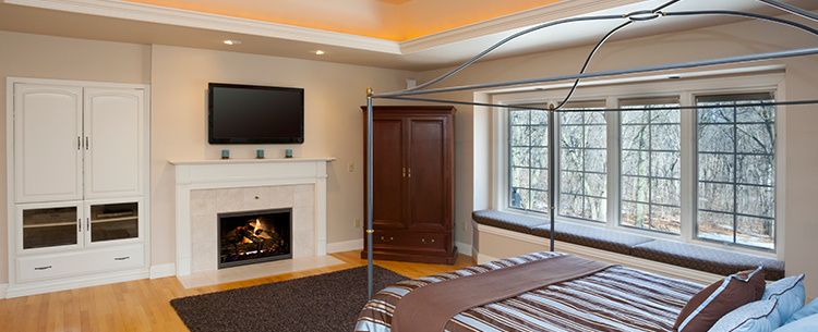 A gorgeous room with a TV above a fireplace.