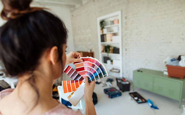 A woman deciding on a colour for her accent furniture using an accent colour wheel.