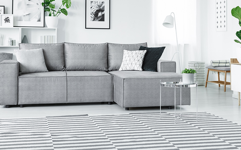 A black-and-white printed rug, perfectly matched to a set of grey couches.