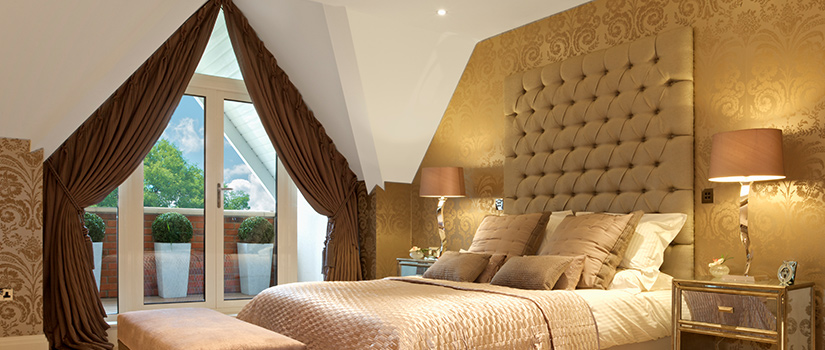 A lavish bedroom with a beautifully upholstered headboard.