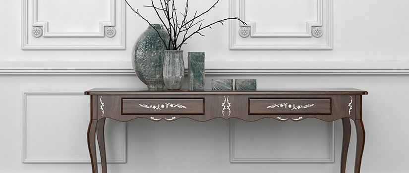 An intricate console table. The surface has a plant, a vase, and two other objects.