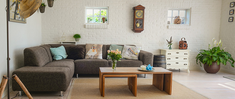 A mixed and matched selection of pillows on a grey sectional couch, with wooden nesting table in the middle.