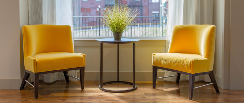 A minimalist side table between two yellow chairs.